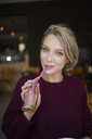 Portrait of smiling blond woman drinking with straw from bottle in a cafe - PNEF00744