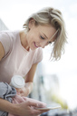 Happy blond woman with takeaway coffee looking at cell phone in the city - PNEF00747