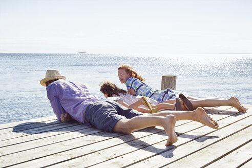 Family lying on pier, Utvalnas, Gavle, Sweden - CUF42678