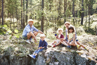 Family sitting on rocks in forest - CUF42690