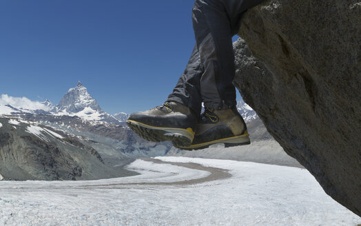 Man sitting on rock by the Matterhorn, Zermatt, Canton Wallis, Switzerland - CUF42730