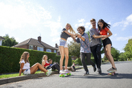 Group of young adults having fun on skateboards - CUF42782