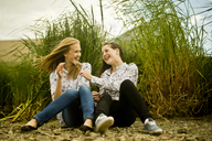 Two young women laughing in breeze - CUF42794