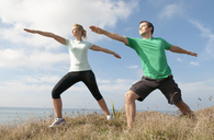 Mid adult couple exercising on cliff top, Thurlestone, Devon, UK - CUF42812