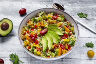 Bowl of bulgur salad with bell pepper, tomatoes, avocado, spring onion and parsley - SARF03836