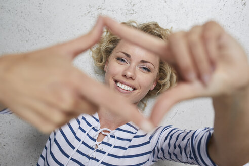 Portrait of smiling blond woman shaping frame with her fingers - PNEF00753
