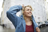 Portrait of smiling blond woman putting on her hood - PNEF00759