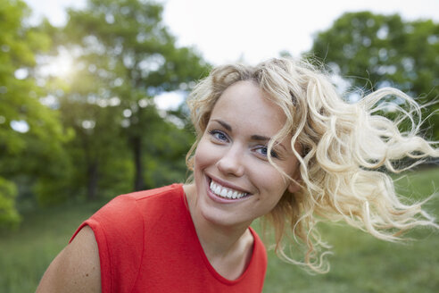Portrait of smiling blond woman  wearing red t-shirt outdoors - PNEF00762