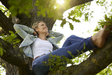 Smiling blond woman relaxing in nature - PNEF00765