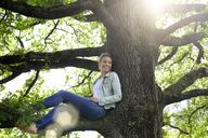 Smiling woman sitting on branch relaxing - PNEF00768