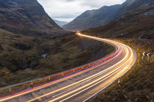 UK, Scotland, car light trails on scenic road through the mountains in the Scottish highlands near Glencoe at dusk - WPEF00687