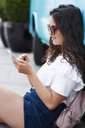 Smiling young woman sitting outdoors using cell phone - ABIF00675
