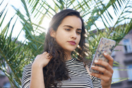 Young woman using cell phone in front of a plant - ABIF00681