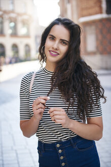 Portrait of smiling young woman in the city - ABIF00687