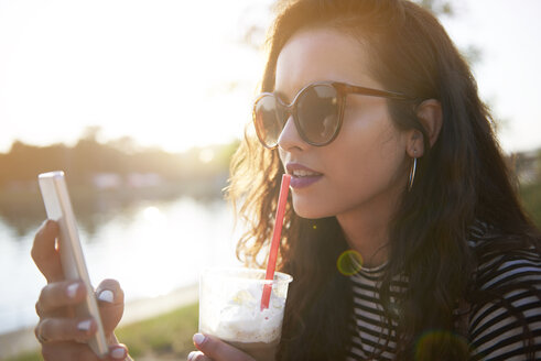 Stylish young woman with cell phone and takeaway drink outdoors at sunset - ABIF00693