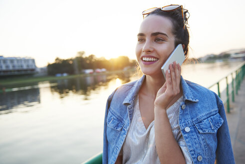 Smiling young woman on cell phone at the riverside at sunset - ABIF00696