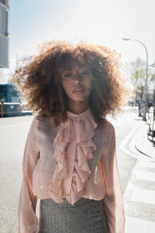 Portrait of beautiful young woman with afro hairdo in the city - MAUF01487