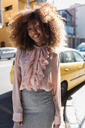 Portrait of smiling beautiful young woman with afro hairdo in the city - MAUF01490