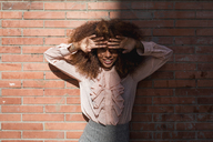 Portrait of smiling beautiful young woman with afro hairdoat brick wall in sunshine - MAUF01493