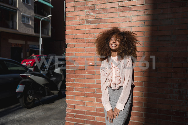 Portrait of smiling young woman with afro hairdo leaning against brick wall in the city - MAUF01496