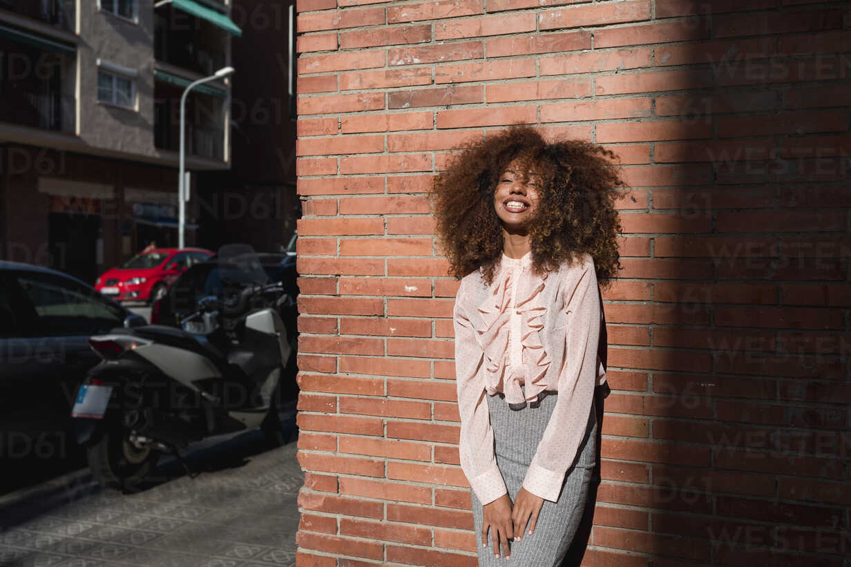 Portrait of smiling young woman with afro hairdo leaning against brick wall in the city - MAUF01496 - Mauro Grigollo/Westend61