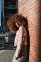 Portrait of beautiful young woman with afro hairdo leaning against brick wall in the city - MAUF01499