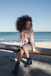 Beautiful young woman with afro hairdo sitting on a bench at the beach - MAUF01502