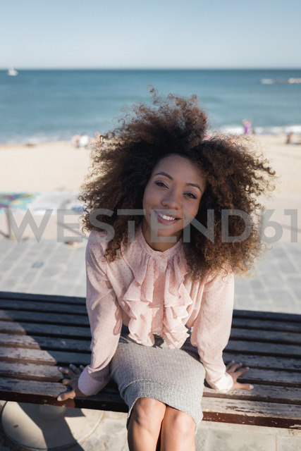 Portrait of smiling beautiful young woman with afro hairdo sitting on a bench at the beach - MAUF01505