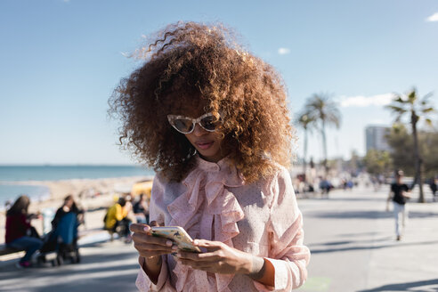 Stylish young woman using cell phone at seaside promenade - MAUF01508