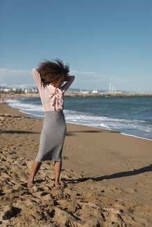 Young woman with afro hairdo standing on the beach - MAUF01514