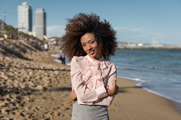 Portrait of smiling beautiful young woman with afro hairdo standing on the beach - MAUF01517