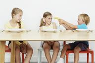 Three children at table, boy holding banana - CUF42959