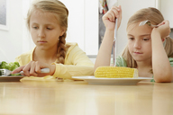 Girls poking vegetables on plate - CUF42968