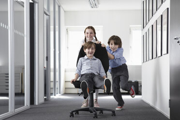 Three children playing in office corridor on office chair - CUF42983