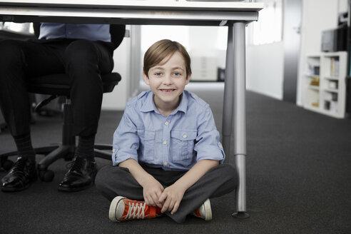 Boy sitting on floor with businessman working at desk - CUF42998