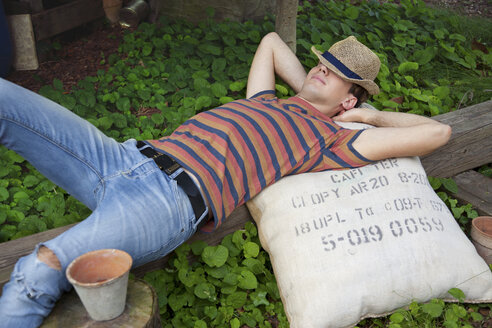 Young man wearing straw hat lying on sack - CUF43100