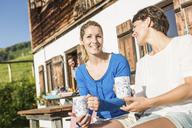 Two women drinking coffee outside chalet, Tyrol, Austria - CUF43139