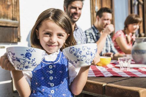 Girl holding breakfast cups outside chalet, Tyrol, Austria - CUF43151