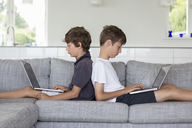 Brothers back to back on sofa using computers - CUF43193