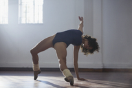 Strong young female dancer practicing in dance studio - HOXF03628