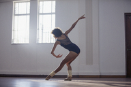 Graceful young female dancer practicing in dance studio - HOXF03649