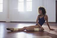 Strong young female dancer stretching leg in dance studio - HOXF03658