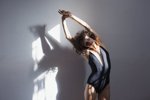 Sensual young female dancer stretching in sunlight at wall - HOXF03664