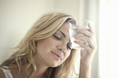 Close up portrait of young woman with glass of water - CUF43353