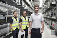 Portrait of three workers in engineering warehouse - CUF43410