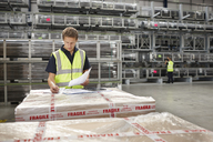 Warehouse worker checking order in engineering warehouse - CUF43416