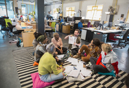 Creative business people meeting, brainstorming in circle on floor in office - CAIF20994