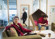 Portrait confident creative businesswoman working in open plan office - CAIF21021