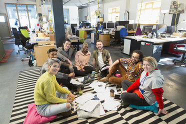 Portrait confident creative business team meeting, brainstorming in circle on office floor - CAIF21048