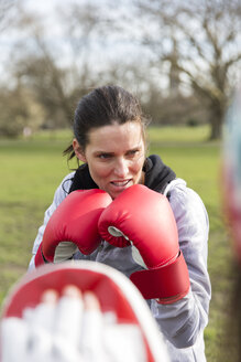 Focused, determined woman boxing in park - CAIF21135